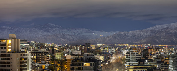 Panel Szklany Amazing views of Santiago de Chile skyline by night with the Andes mountain range full of snow and the ski resorts working at full capacity making a wonderful horizon on a high resolution panorama
