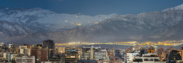 Fototapeta Amazing views of Santiago de Chile skyline by night with the Andes mountain range full of snow and the ski resorts working at full capacity making a wonderful horizon on a high resolution panorama