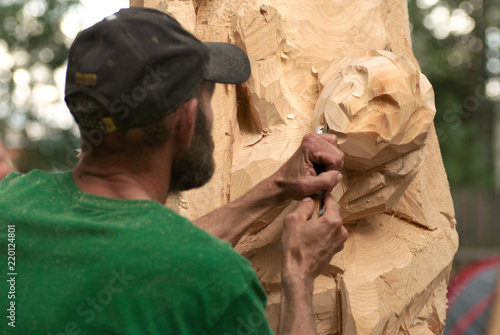 Woodcarver make his sculpture by the chisel. Photo from a carpenter's contest. Selective focus.