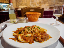 Wide Closeup Of A Plate Of Squid Seafood Bolognese Spaghetti With A Glass Of White Wine At A Table At An Italian Restaurant, Paris, France. Travel And Cuisine.