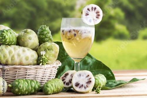 Photo Noni fruit or Morinda Citrifolia with noni juice and leaf in the basket for health on the wooden table background with copy space for text