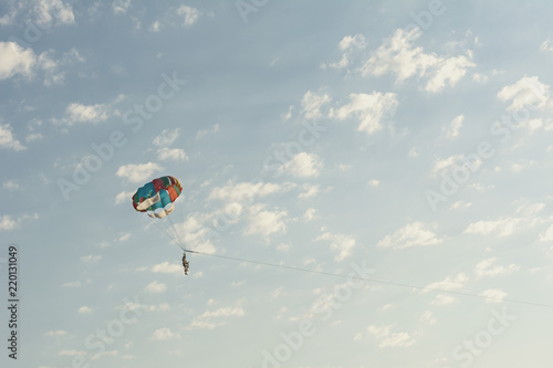 Foto op Canvas Luchtsport Round parachute against the sunset sky with clouds in an unusual color scheme. Multi-color process.