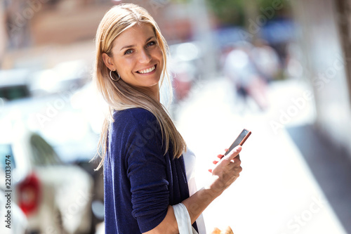 Fotografía  Beautiful young woman looking at the camara while using her smartphone in the street