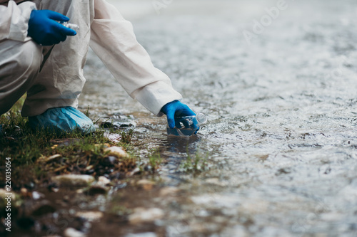 Obraz Scientist in protective suite taking water samples from the river. - fototapety do salonu
