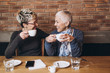 canvas print picture - Senior mother sitting in cafe bar or restaurant with her middle age daughter and enjoying in conversation.