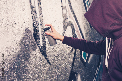 Graffiti artist with aerosol spray bottle near the wall © stasnds