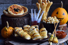 Halloween Trick Or Treat Party. Funny Delicious Food And Pumpkin On Wooden Background - Mini Pizza, Bread Sticks, Cheese, Olives, Ketchup, Popcorn, Juice. Copy Space For Text.