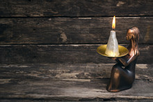 Burning Candle In The Bowl In Hands Of Woman Statuette On Aged Wooden Table Background.