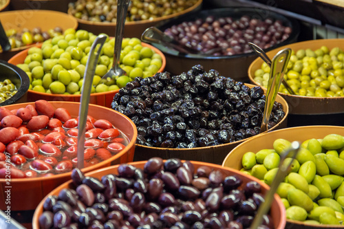 Bowls of green and black olives on display on a market stall