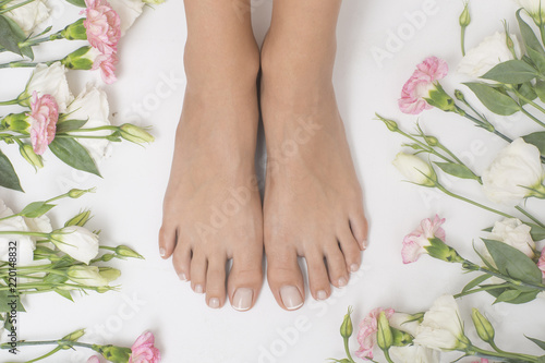 Papiers peints Pedicure The picture of perfectly done pedicure. Foot surrounded by colorful flowers.