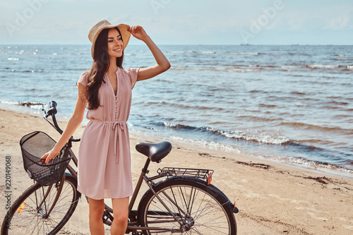 Fototapeta Beautiful brunette girl dressed in dress and hat posing with a bicycle on the beach on a sunny day. obraz na płótnie