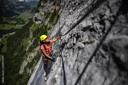 Pretty, female climber on a via ferrata - climbing on a rock in Swiss Alps Canvas Print