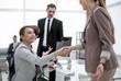 handshake two business women near the desktop