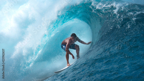 Foto  CLOSE UP: Crystal clear water splashes over surfer riding an epic barrel wave