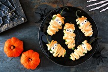 Halloween Mummy Jalapeno Poppers, Top View With Decor On A Dark Stone Background