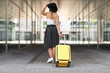 Young woman with yellow carry on suitcase outdoors
