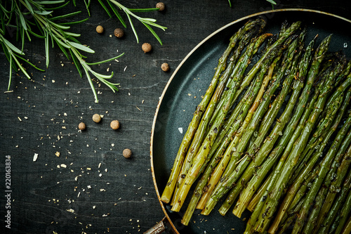 Fotografiet  delicious green asparagus in a pan on a wooden black table with rosemary and sal