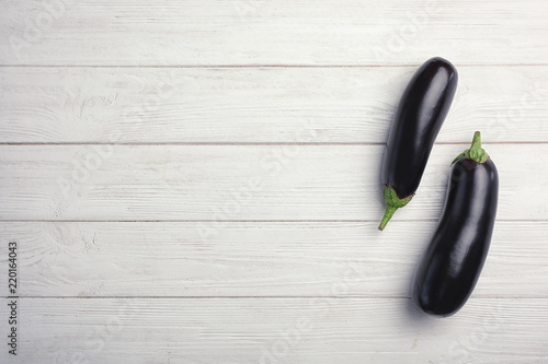 Raw ripe eggplants on wooden background, top view