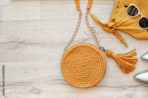 Valokuva  Stylish set with knitted bag and space for design on wooden background, flat lay