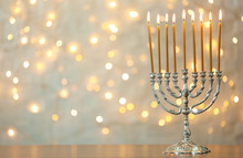 Hanukkah Menorah With Candles On Table Against Blurred Lights