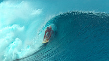 CLOSE UP: Large Emerald Ocean Wave Splashes Over The Cheerful Extreme Surfer.