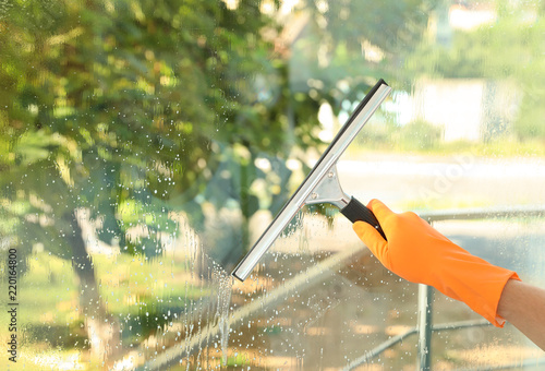 Janitor cleaning window with squeegee indoors, closeup