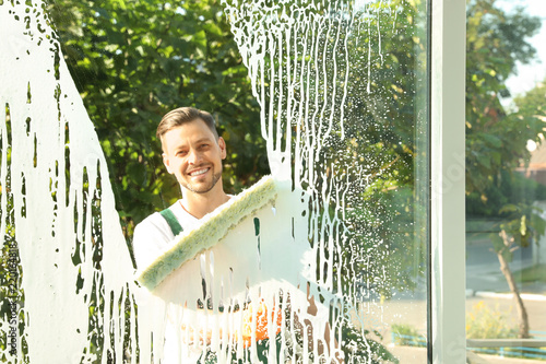Male janitor cleaning window, view from inside