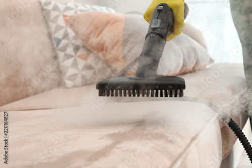 Fototapeta Janitor removing dirt from sofa with steam cleaner, closeup obraz