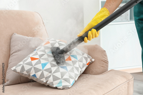 Fototapeta Janitor removing dirt from sofa cushion with steam cleaner, closeup obraz