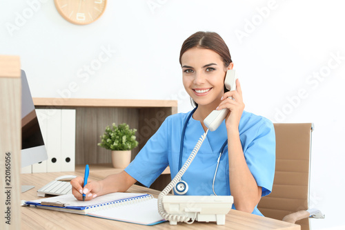 Obraz Female medical assistant at workplace in clinic. Health care service - fototapety do salonu