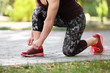 Young woman tying shoelaces before running in park, focus on legs