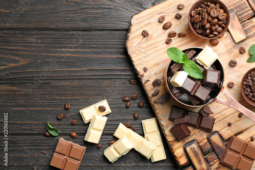 Flat lay composition with different kinds of chocolate on wooden table and space for text