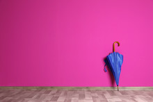 Beautiful Umbrella On Floor Near Color Wall With Space For Design