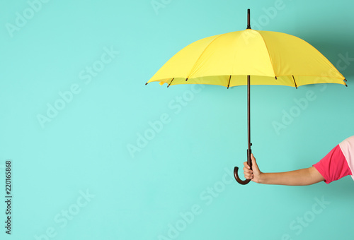 Fotografia  Woman holding beautiful umbrella on color background with space for design