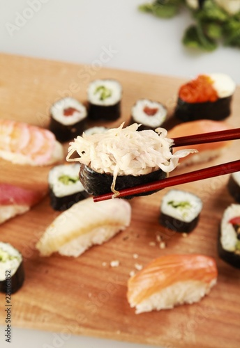 Gunkan Sushi with Chopsticks and Sushi Plate in Background
