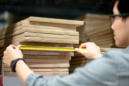Fotografija Young Asian man worker using tape measure for measuring dimension of product in cardboard box