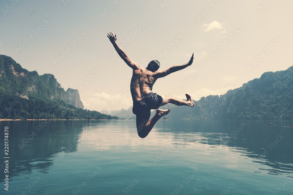 Fototapeta Man jumping with joy by a lake