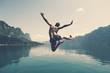 Leinwanddruck Bild - Man jumping with joy by a lake