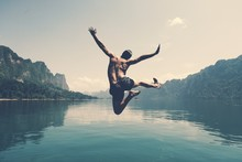 Man Jumping With Joy By A Lake