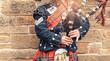 Leinwanddruck Bild - EDINBURGH, SCOTLAND, 24 March 2018 , Scottish bagpiper dressed in traditional red and black tartan dress stand before stone wall. Edinburgh, the most popular tourist city destination in Scotland.