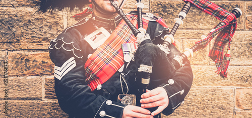 Foto EDINBURGH, SCOTLAND, 24 March 2018 , Scottish bagpiper dressed in traditional red and black tartan dress stand before stone wall