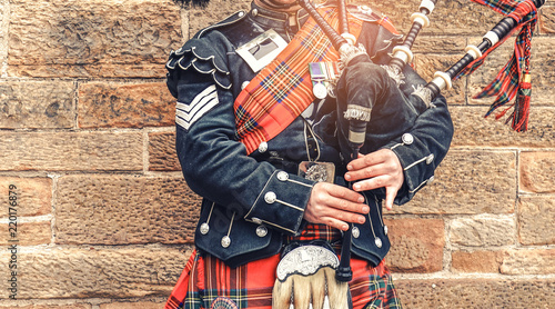 Fotografering EDINBURGH, SCOTLAND, 24 March 2018 , Scottish bagpiper dressed in traditional red and black tartan dress stand before stone wall