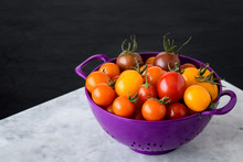 Freshly Picked Heirloom Tomatoes, Yellow, Red, And Purple, In A Purple Plastic Colander On A Gray Marble Slab, Black Background