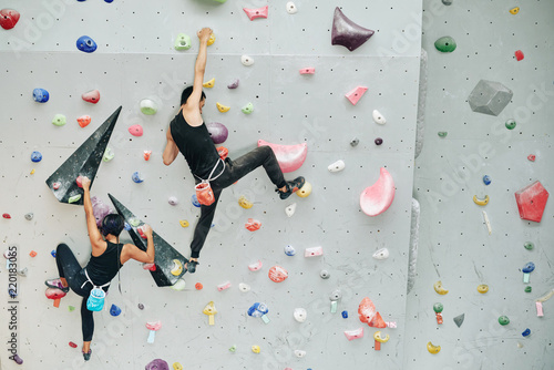 Couple practicing rock climbing on artificial wall indoors
