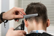 cut hair to the boy on the back of the head using a hair clipper and comb