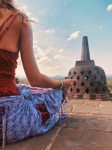 Fotografia  Young woman practicing yoga - meditation on the biggest Buddhist temple - Borobudur