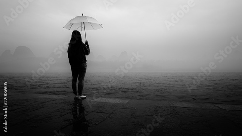 Photo Girl holding umbrella by the river on a foggy morning