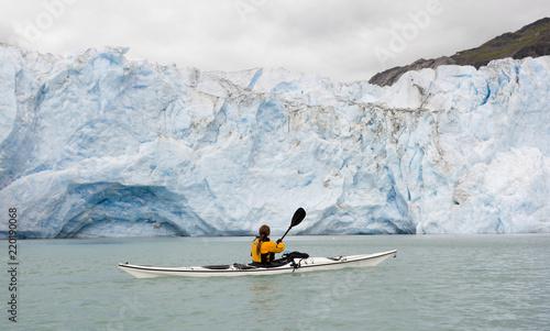 Woman kayaking in front of McBride glacier in Glacier Bay National Park, Alaska, USA