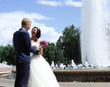 beautiful smiling couple standing near the fountain