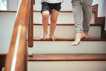 Cropped Image Of Mother And Son Walking Down The Stairs At Home